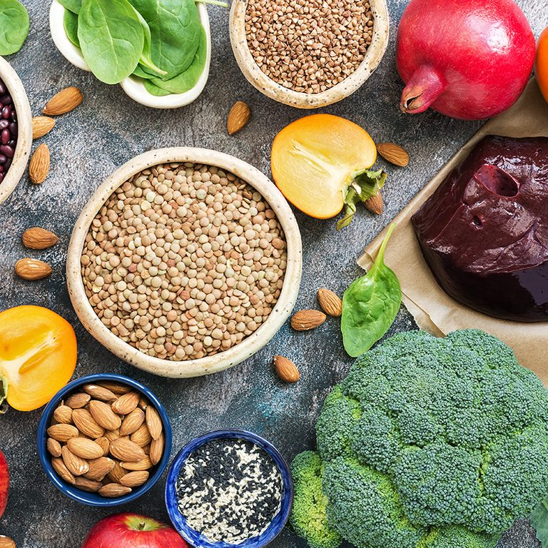 Foods high in iron. liver, broccoli, persimmon, apples, nuts, legumes, spinach, pomegranate. Top view, flat lay