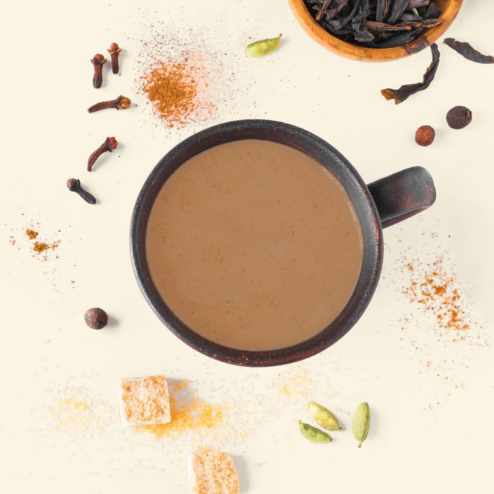 cup of chai tea from overhead with sugar and other ingredients scattered around the mug