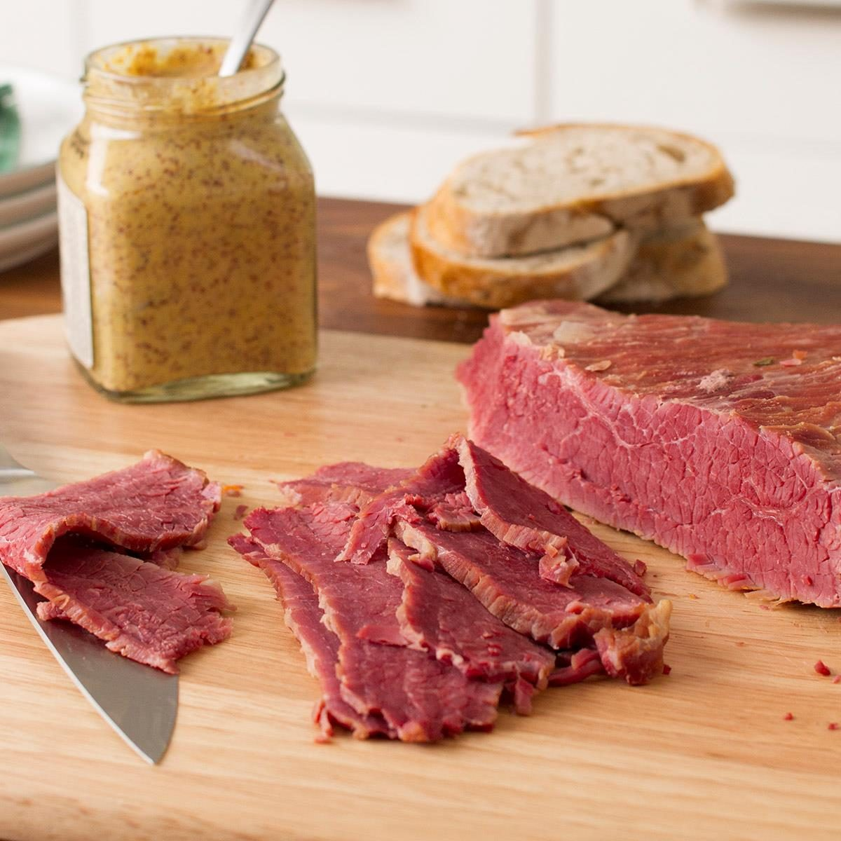 A piece of sliced corned beef brisket on a cutting board. With a jar of mustard and rye bread in the background.