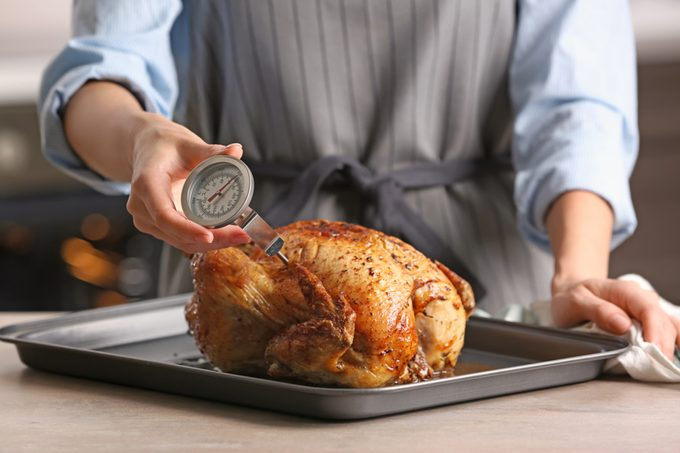 Young woman measuring temperature of whole roasted turkey with meat thermometer; Shutterstock ID 700552579; Job (TFH, TOH, RD, BNB, CWM, CM): TOH