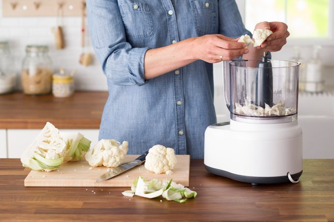 Person pulling pieces of cauliflower apart to place into a blender