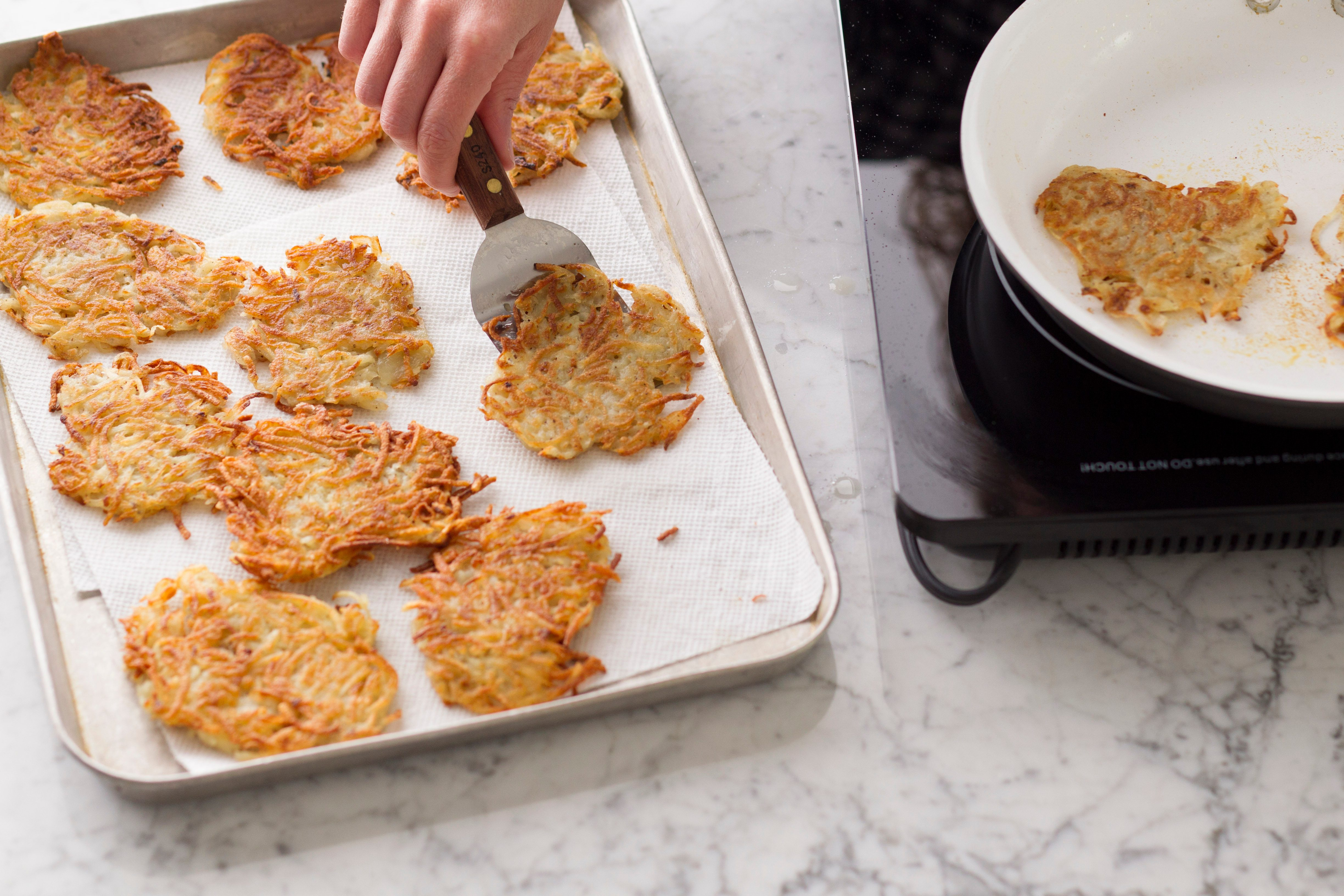 Metal spatula depositing potato pancakes from the skillet to a lined baking sheet