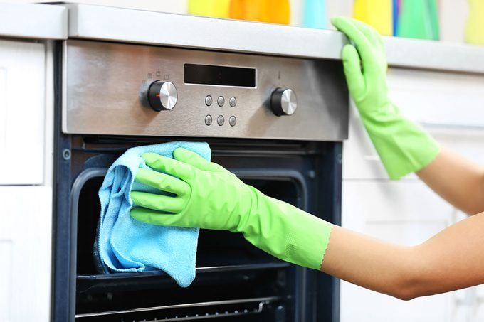Woman hands in protective gloves cleaning oven with rag