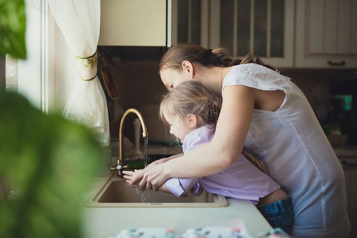 Daughter with her mother to wash their hands in the kitchen sink
