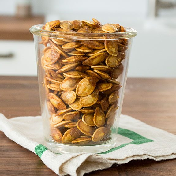 Roasted pumpkin seeds in a glass cup sitting on a wooden table.