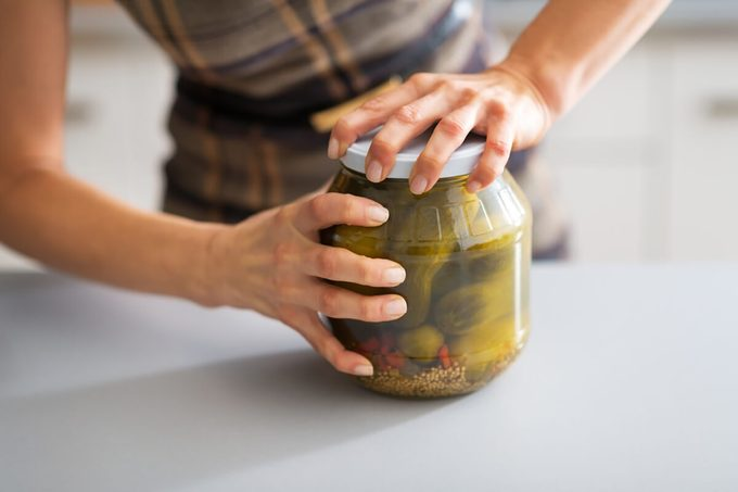 Closeup on young housewife opening jar of pickled cucumbers