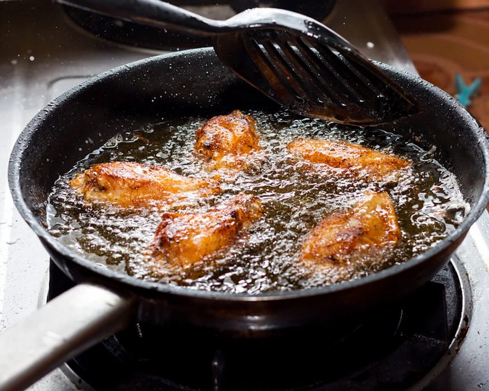 Chicken frying in a pan.