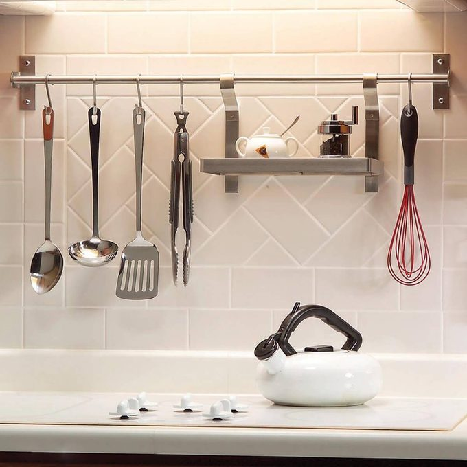 Kitchen tools hanging from a bar over the counter