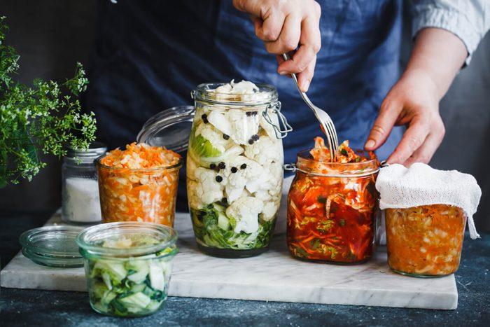 Cabbage kimchi, broccoli marinated, sauerkraut sour glass jars over rustic kitchen table.
