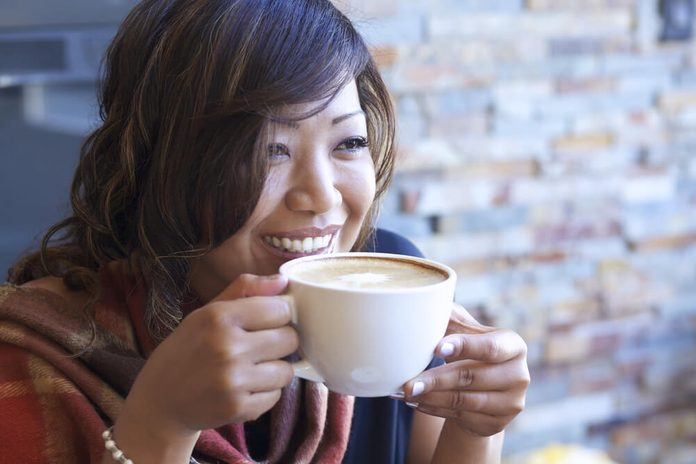 Portrait of beautiful Asian woman drinking cappuccino at a coffee shop.