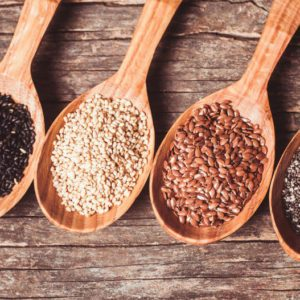 Chia and flax seeds, white and black sesame in wooden spoons