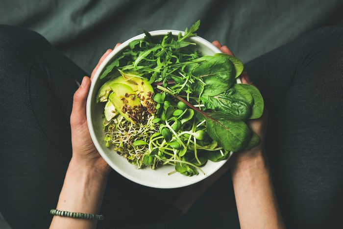 Green vegan breakfast meal in bowl with spinach, arugula, avocado, seeds and sprouts.
