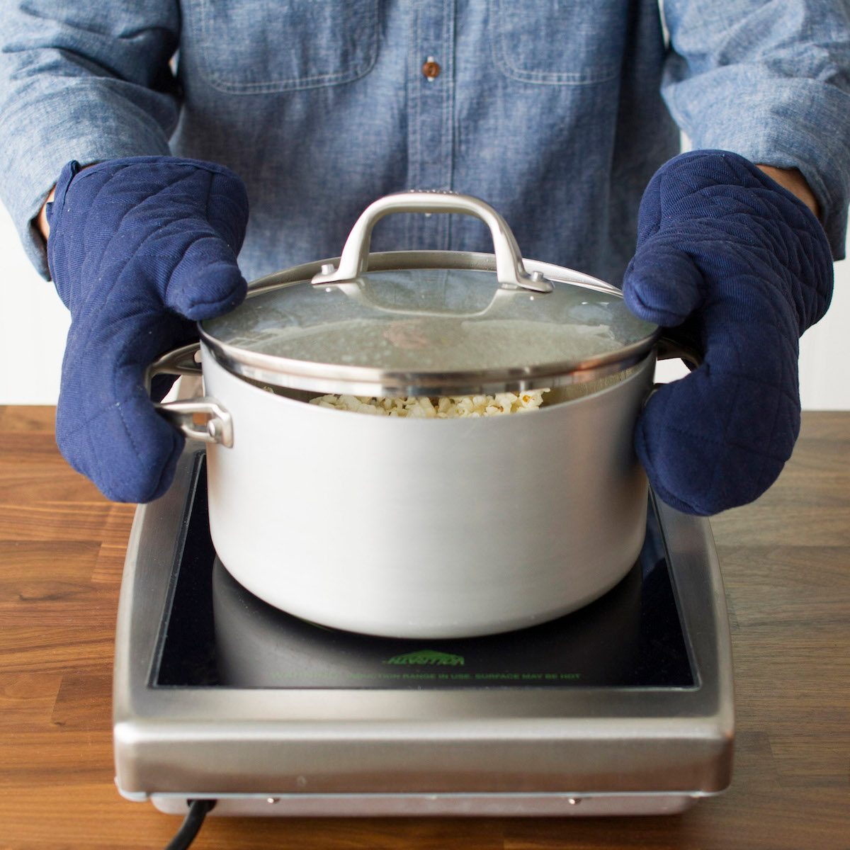A person wearing oven mitts and shaking a pot of homemade stovetop popcorn over an electric burner.