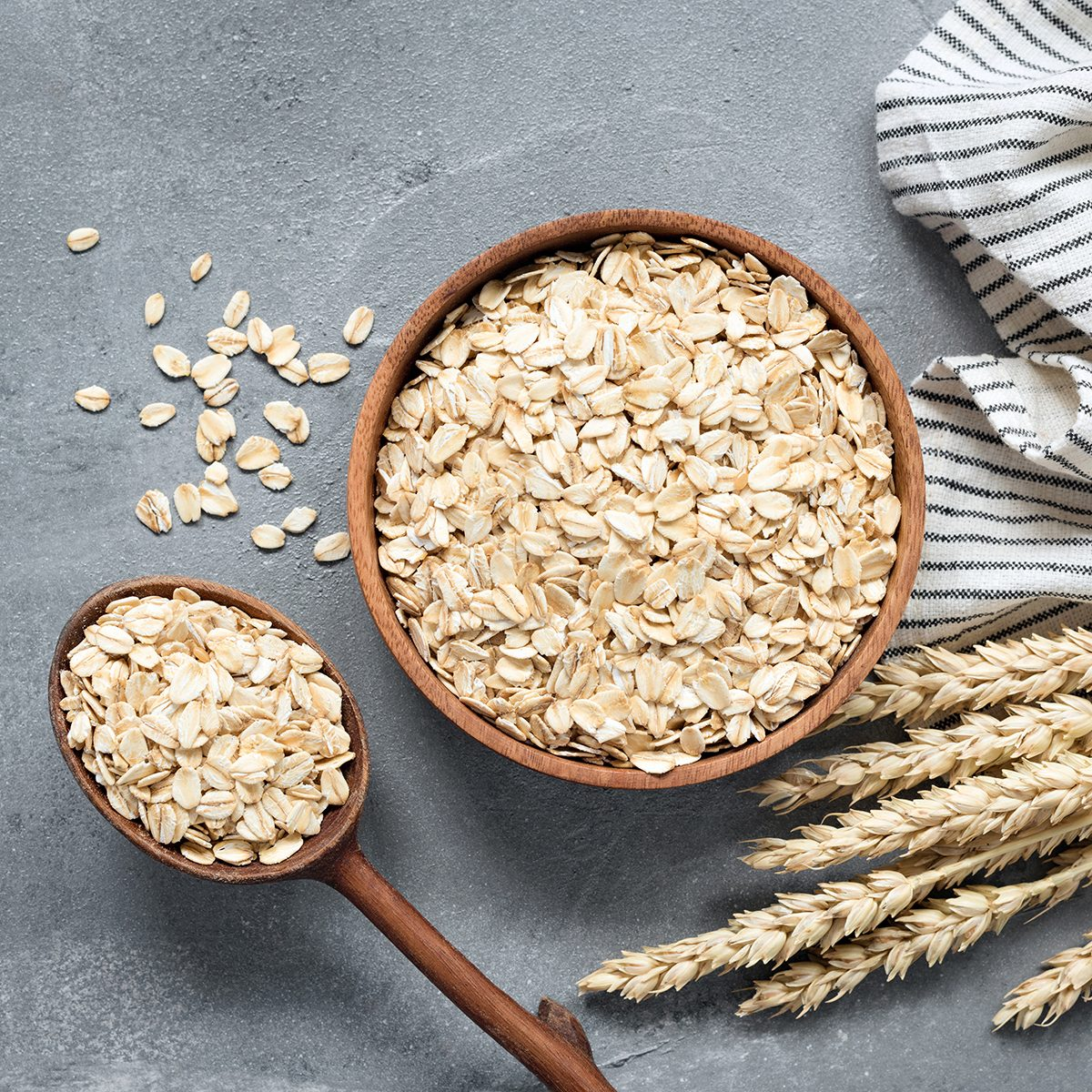 Oats, rolled oats or oat flakes in wooden bowl and wooden spoon. Top view. Healthy grains, low carb diet food