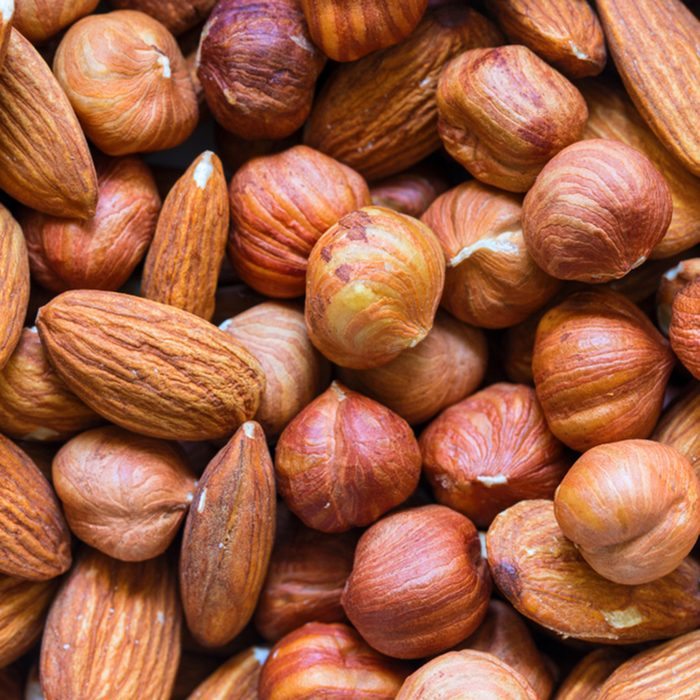 Nuts pile background. Cashew, almond, hazelnut mix closeup. Organic food rustic banner template. Tasty healthy snack. Scattered nut on table top view. Nut assortment flat lay. Nut texture. Nut package; Shutterstock ID 1023253438