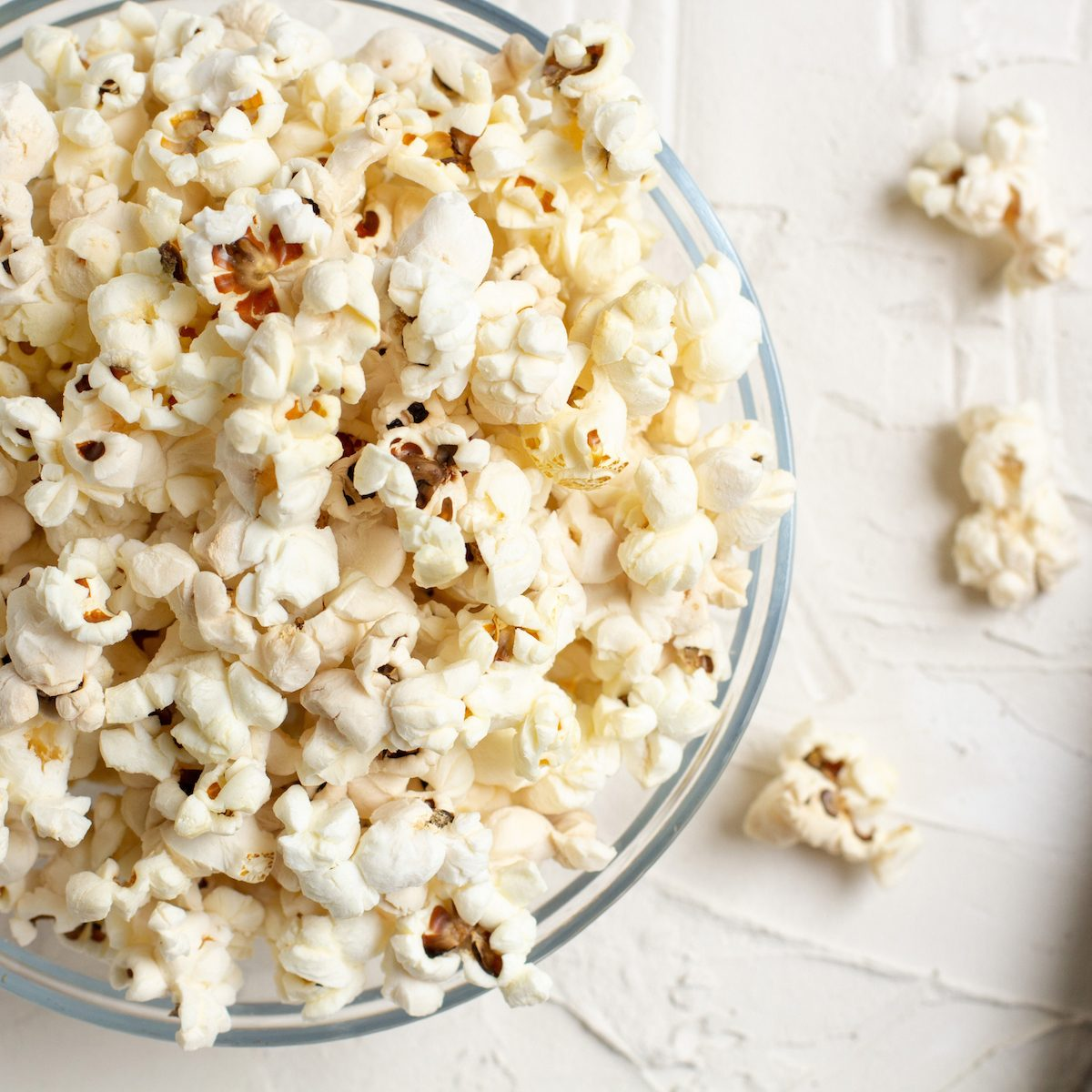 Popcorn in a transparent glass bowl on a white table with few pieces of popcorn beside the bowl.
