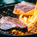 Two t-bone florentine beef steaks on the grill with flames