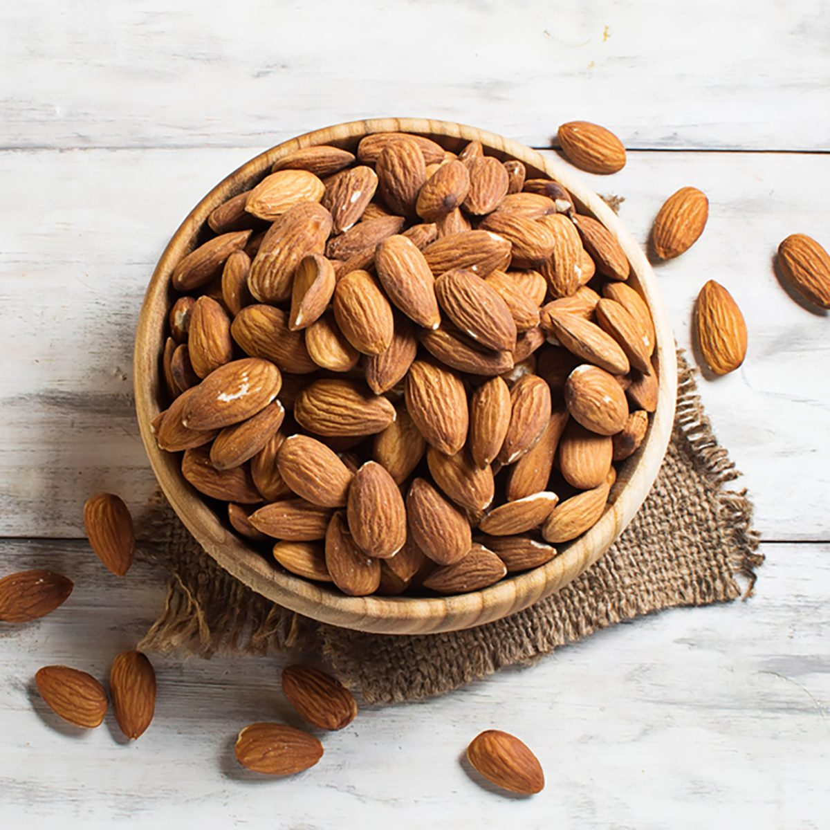 Almonds in brown bowl on wooden background