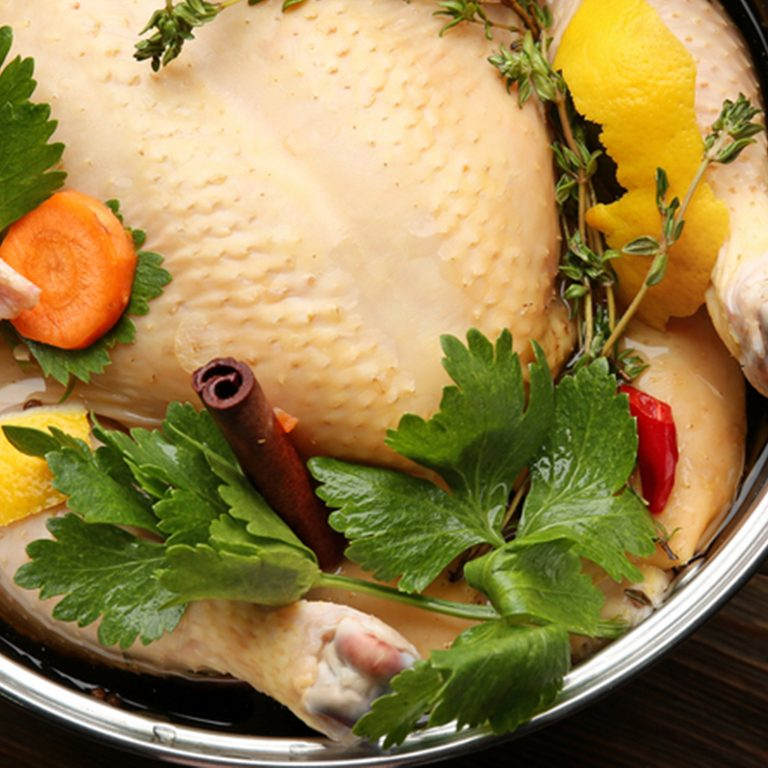 Cooking pot with turkey soaked in flavored brine on wooden table