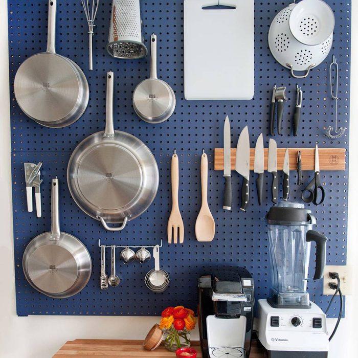 Kitchen with a blue pegboard backsplash