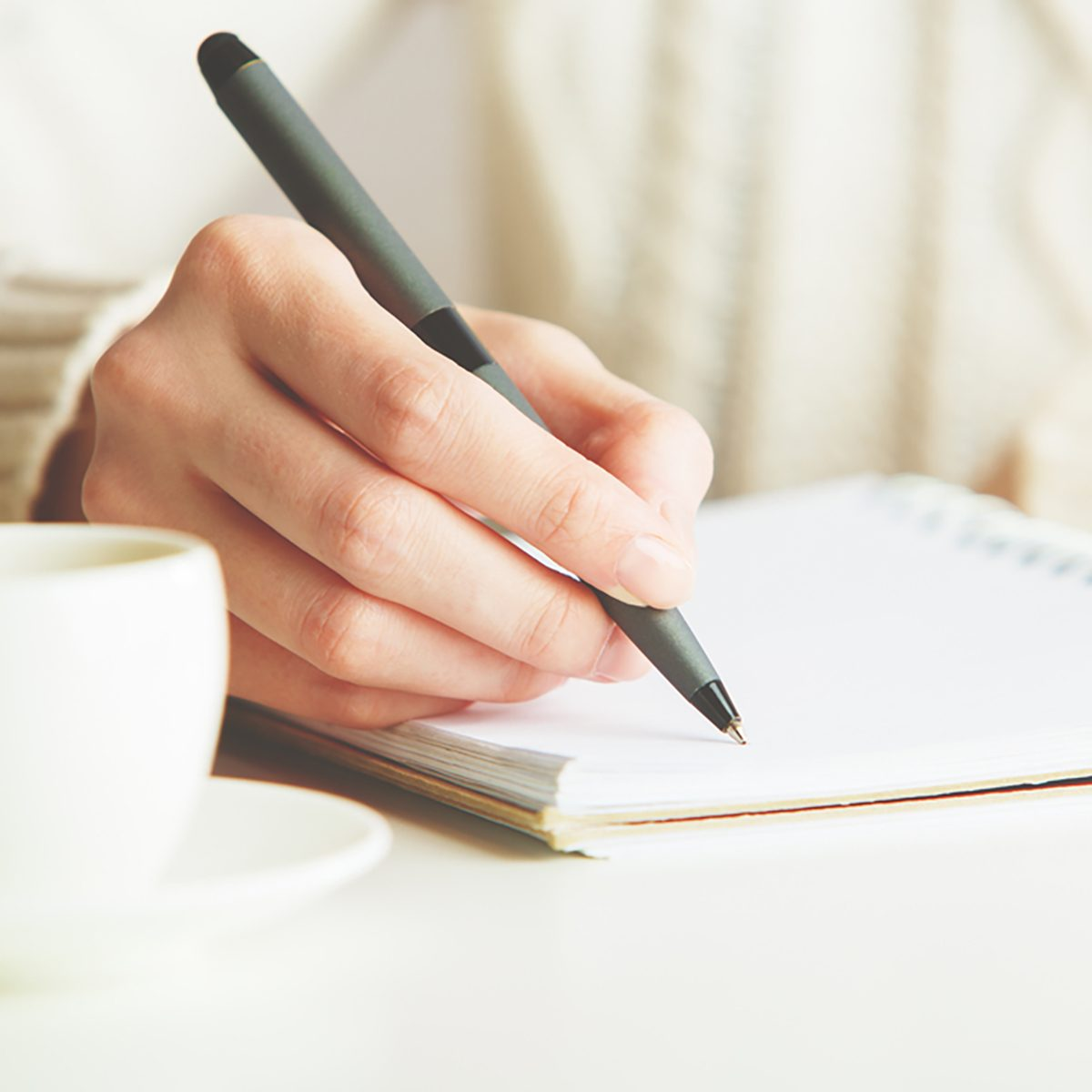 Woman writing in spiral notepad placed on bright desktop with coffee cup.