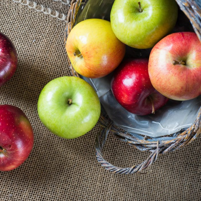 Apples in a basket on burlap and wooden background