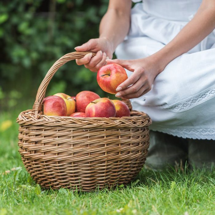Child leaning down to put an apple in a basket