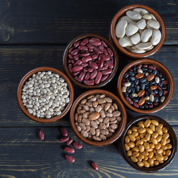 Assortment of beans on black wooden background.
