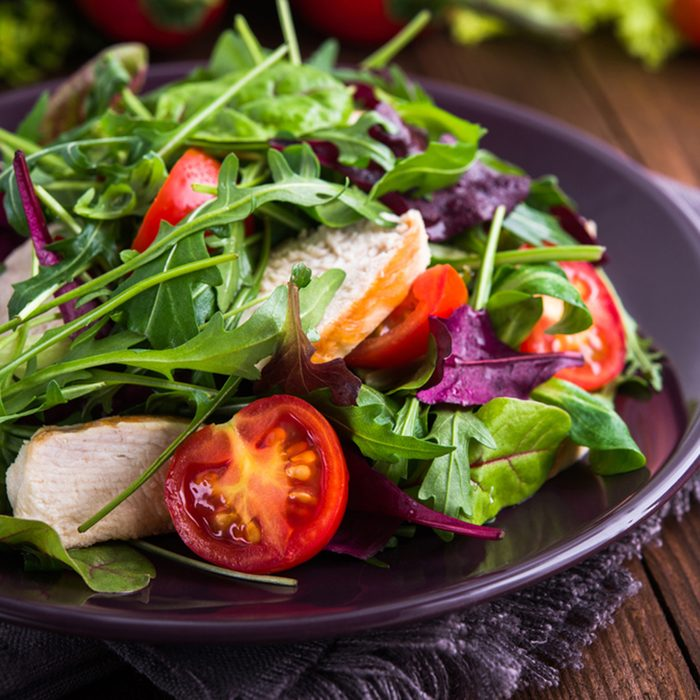 Fresh salad with chicken, tomatoes and mixed greens (arugula, mesclun, mache) on wooden background close up.