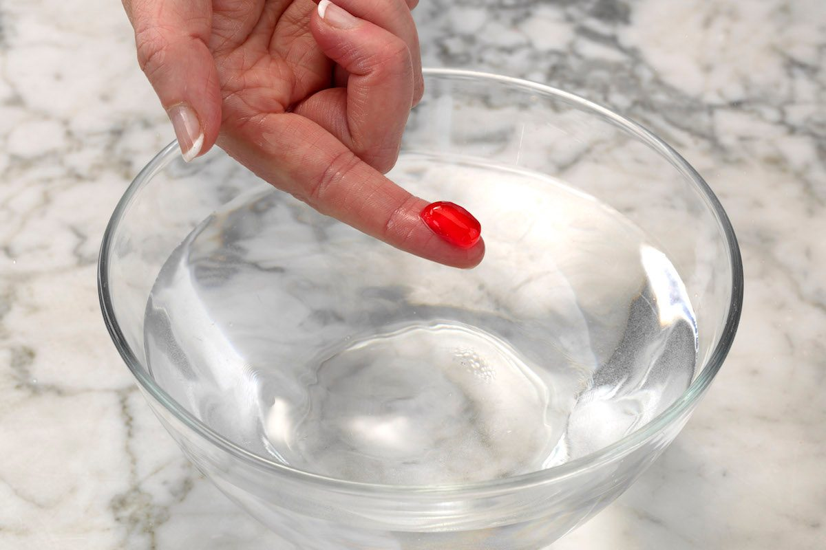 Testing red homemade candy using the cold water test. The mixture forms a ball when dipped in cold water and holds its shape after being removed, which means it's in firm-ball stage.