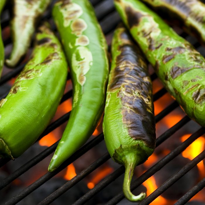 Fresh anaheim chili peppers roasting over a charcoal grill