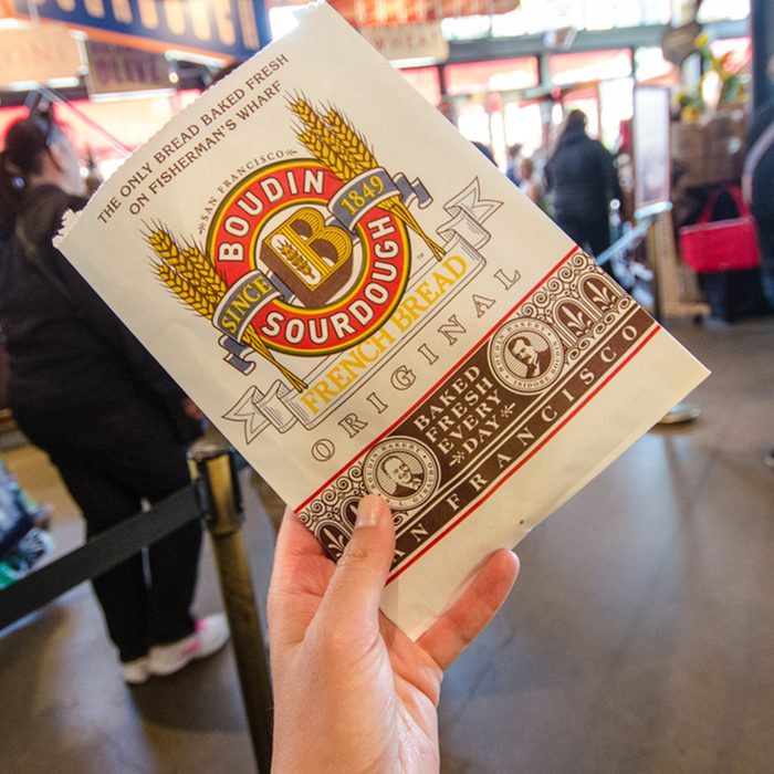 A hand holds up a Boudin Bakery cookie package from the famous sourdough bread restaurant and store.