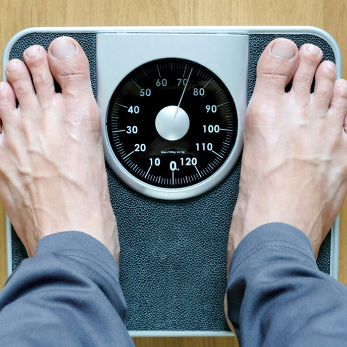 Legs of men standing on scales weight background fitness room.