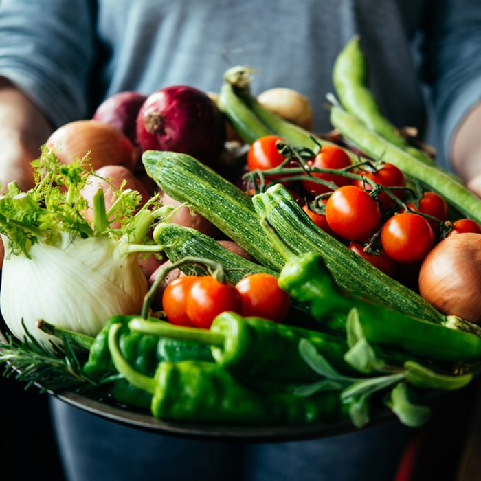 Hands holding big plate with different fresh farm vegetables.
