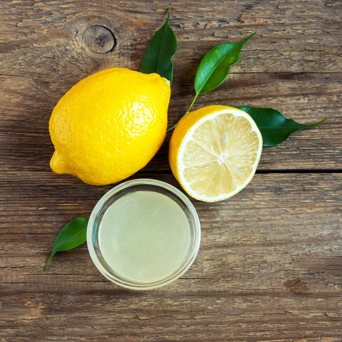 Fresh lemon juice in small bowl and lemons over rustic wooden background