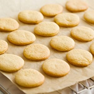 Orange butter cookies on a baking paper and wire rack.