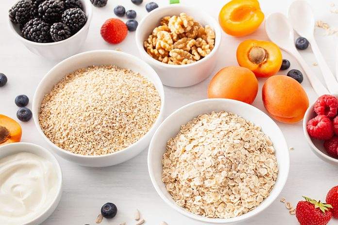 variaty of raw cereals, fruits and nuts for breakfast. Oatmeal flakes and steel cut, barley, walnut, chia, apricot, strawberry.