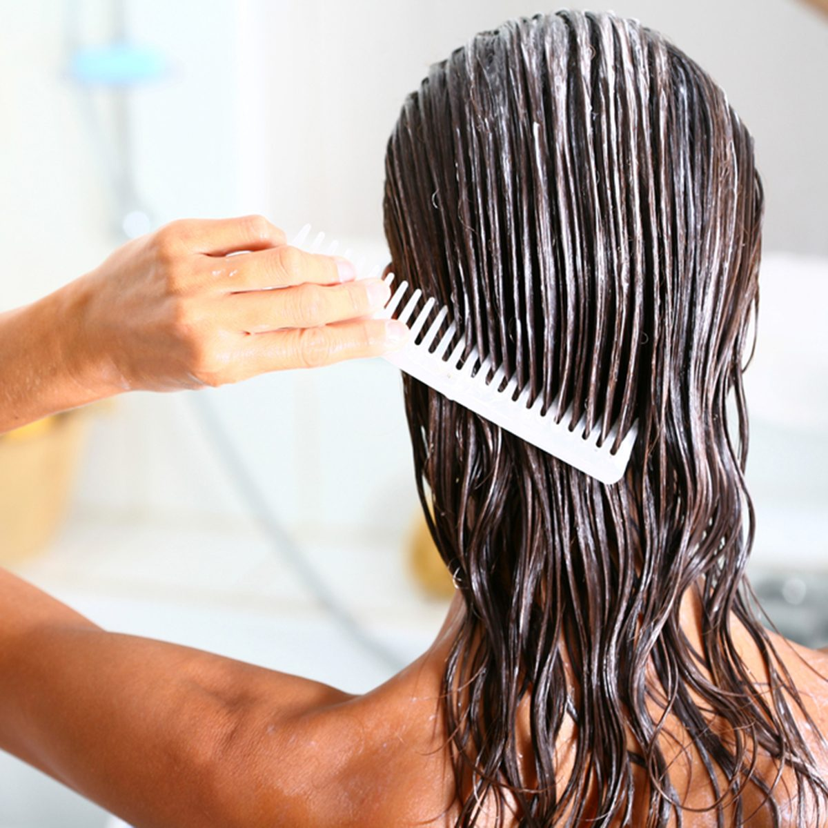 woman applying hair care with a comb