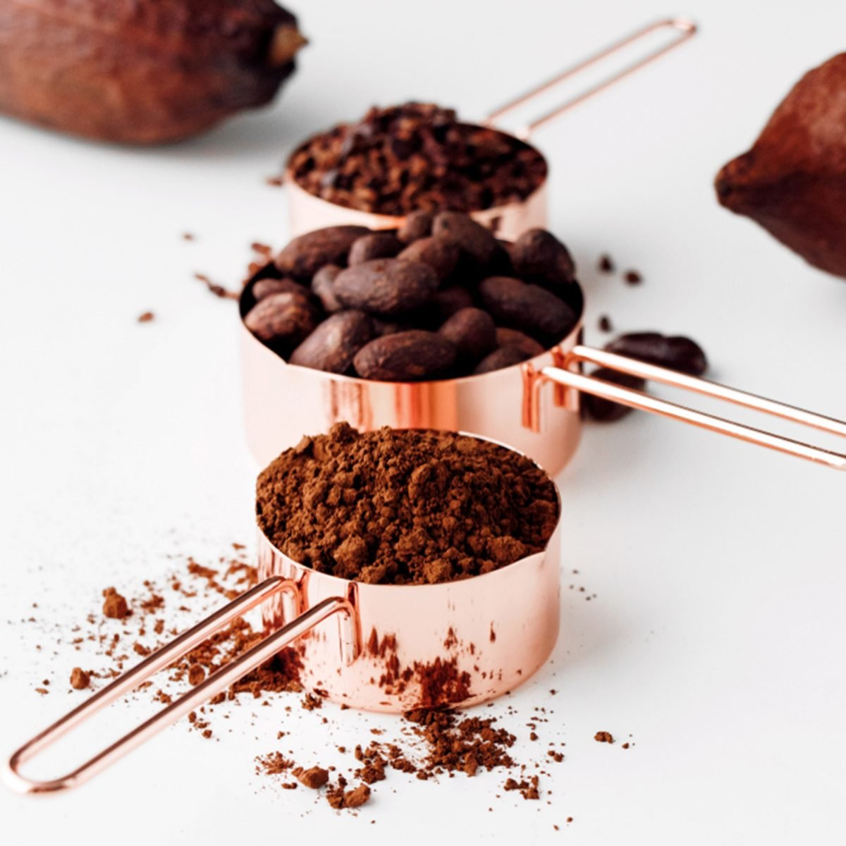 Rose gold measuring cups of cocoa beans, cacao nips, cocoa powder and cocoa pods on a white background