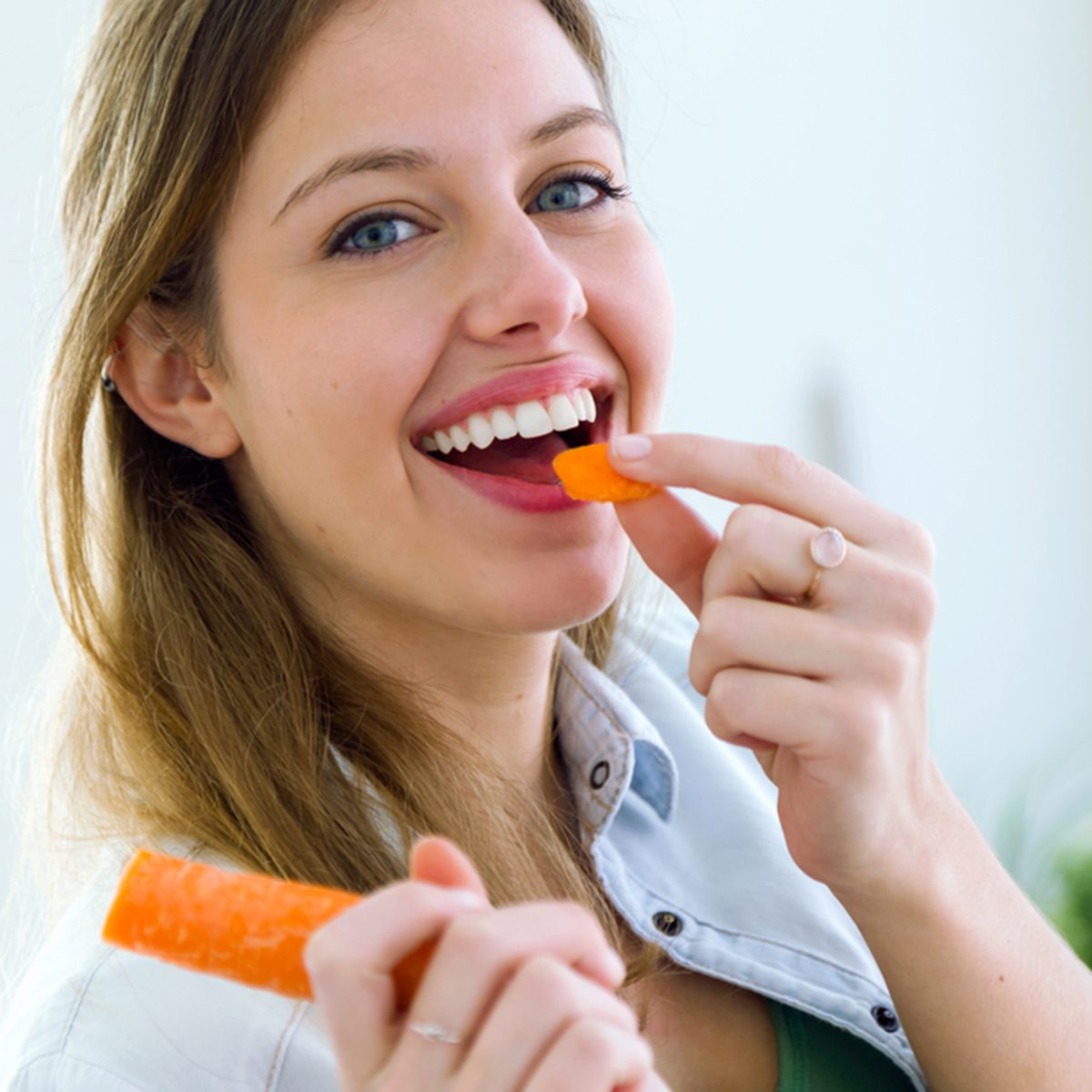 Portrait of pretty young woman eating carrot in the kitchen.