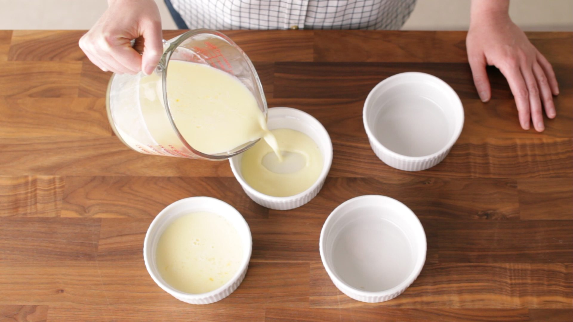 Pouring custard from a measuring cup into custard cups