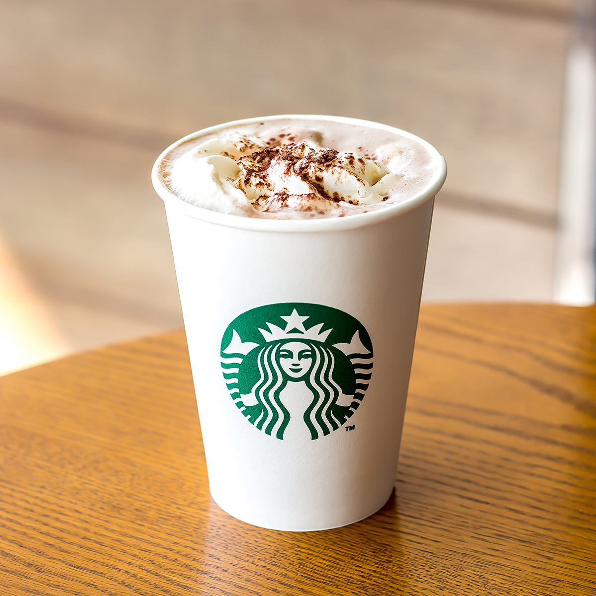 Starbucks Hot chocolate and whipping cream in white paper cup on wooden table
