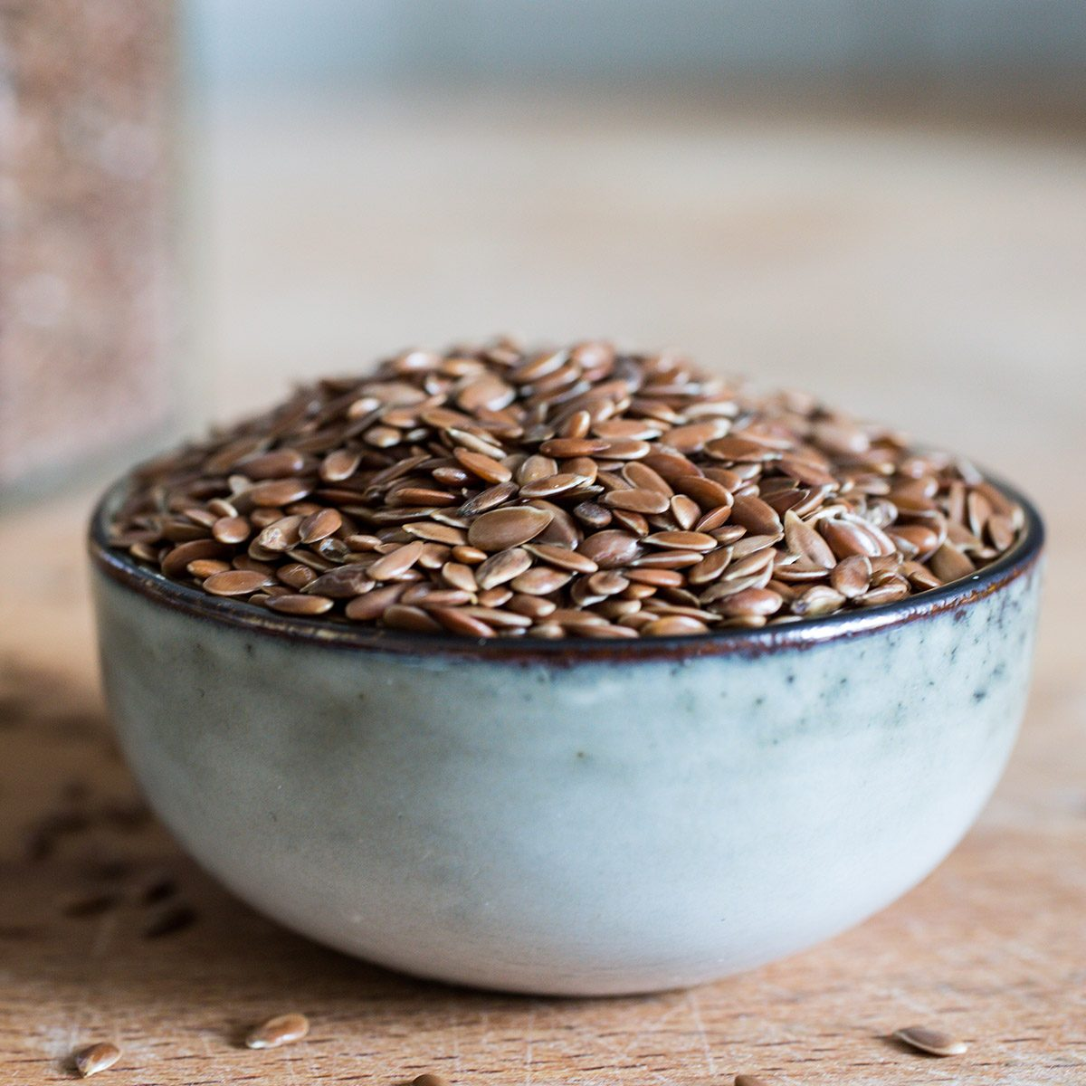bowl on wooden table with superfood healthy linseed flaxseed grain cereal