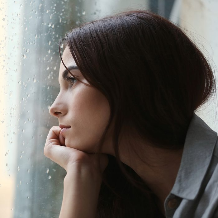 Depressed young woman near window at home