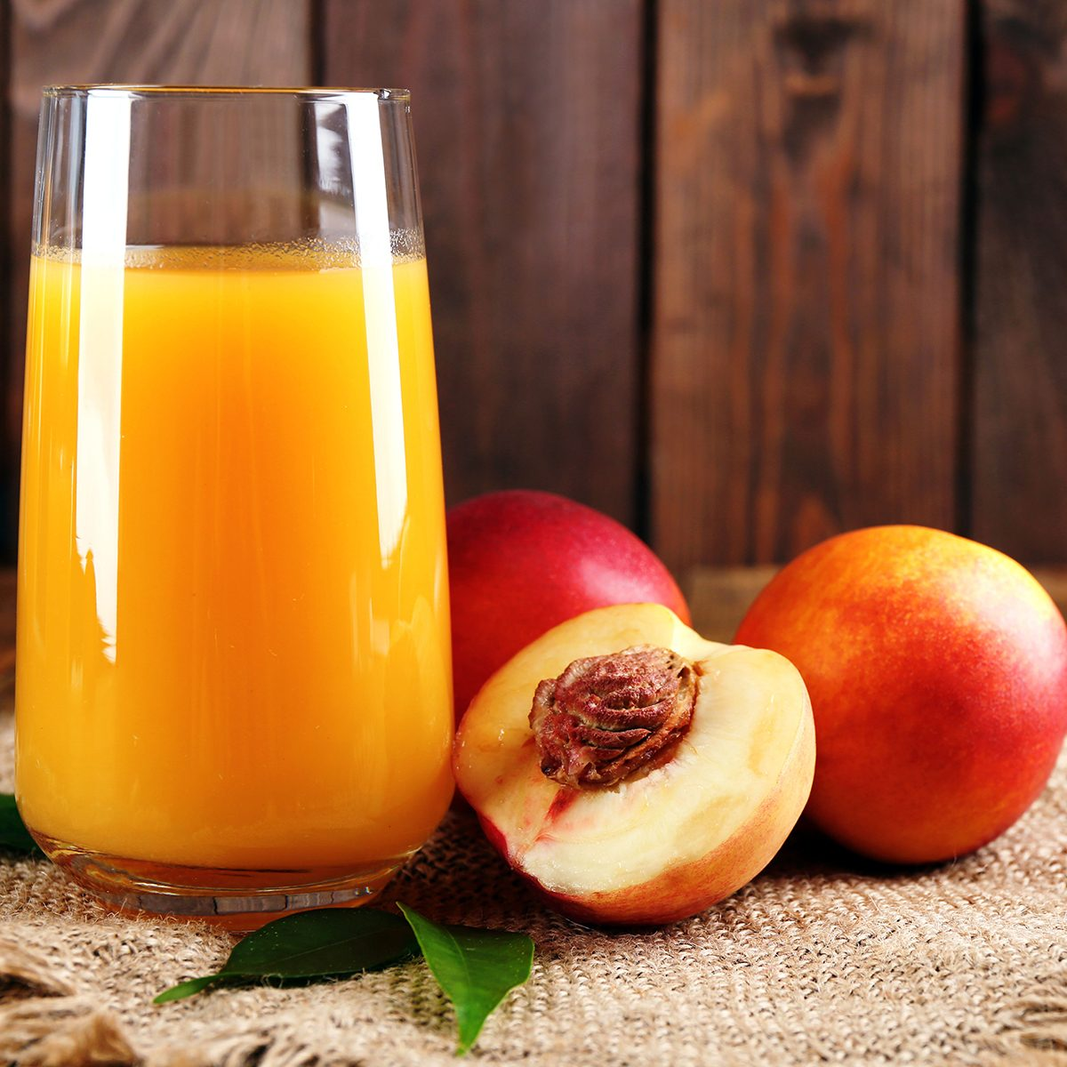 Ripe peaches and glass of juice on wooden background