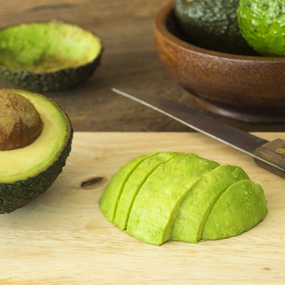 fruits for diabetics avocado and Sliced avocado slices on wooden board