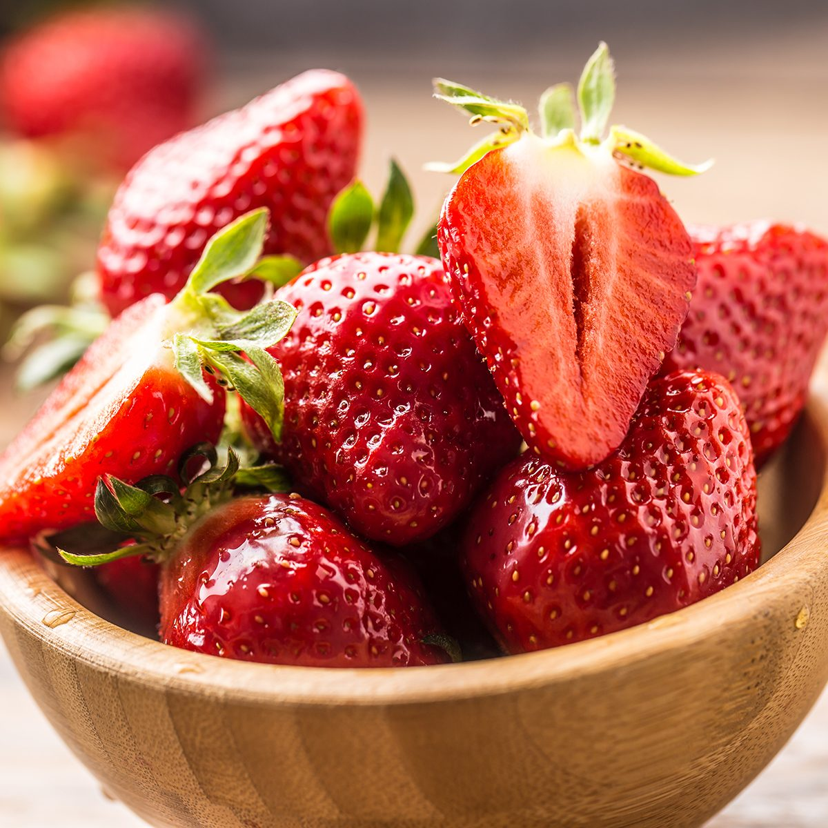 fruits for diabetics Juicy washed strawberries in wooden bowl on kitchen table.