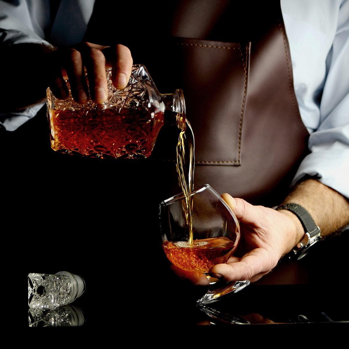 the man pours some brandy into a glass behind the bar
