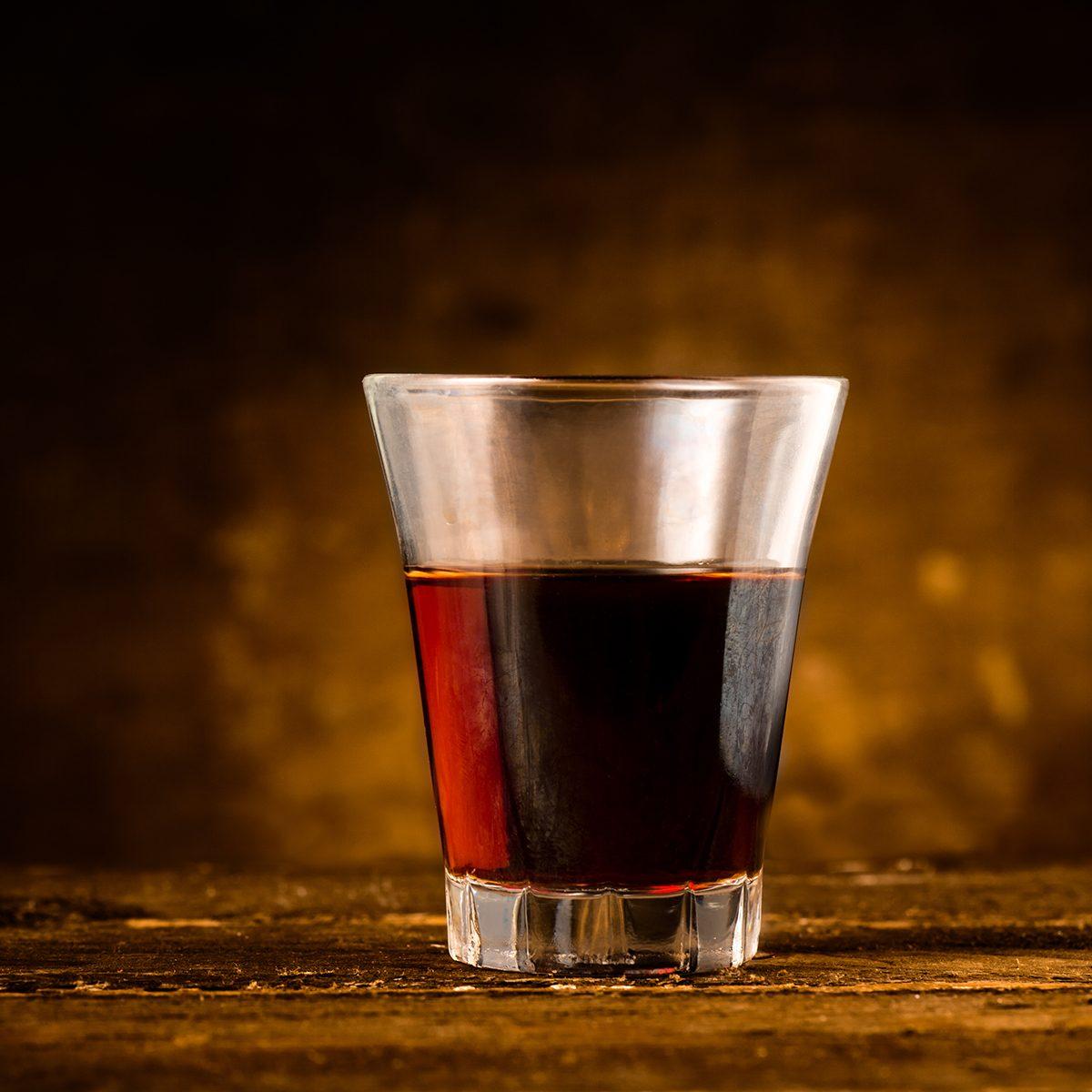 Shot of Alcoholic Bitter Liquor on Wooden Surface