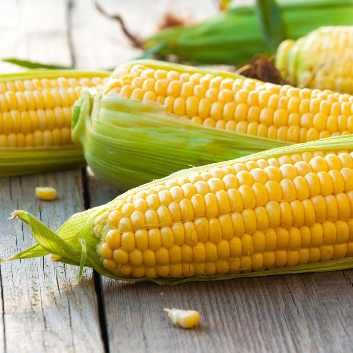 High-fiber foods: Fresh corn on cobs on wooden table, closeup, top view; Shutterstock ID 473507224; Job (TFH, TOH, RD, BNB, CWM, CM): Taste of Home